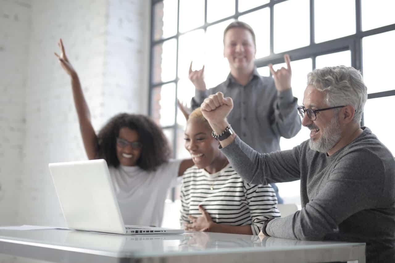 Team around laptop celebrating, digital marketing partner, ROI